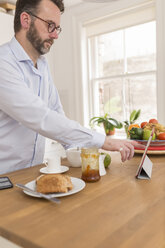 Man standing at breakfast table in the kitchen using digital tablet - BOYF000267