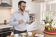 Man standing in the kitchen with cup of coffee looking at his smartphone - BOYF000279