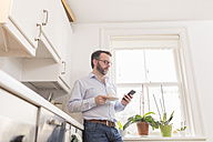 Man standing in the kitchen with cup of coffee looking at his smartphone - BOYF000282
