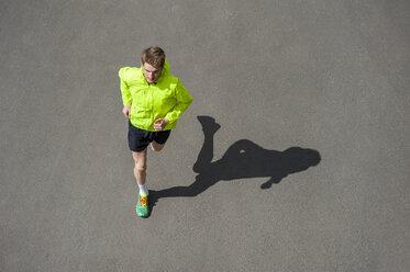 Young man jogging, concrete floor - DIGF000250