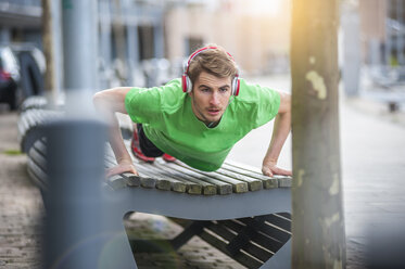 Young sporty man with headphones doing pushups on bench - DIGF000253