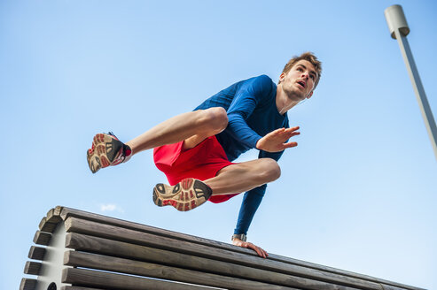 Young sporty man jumping over a bench - DIGF000259