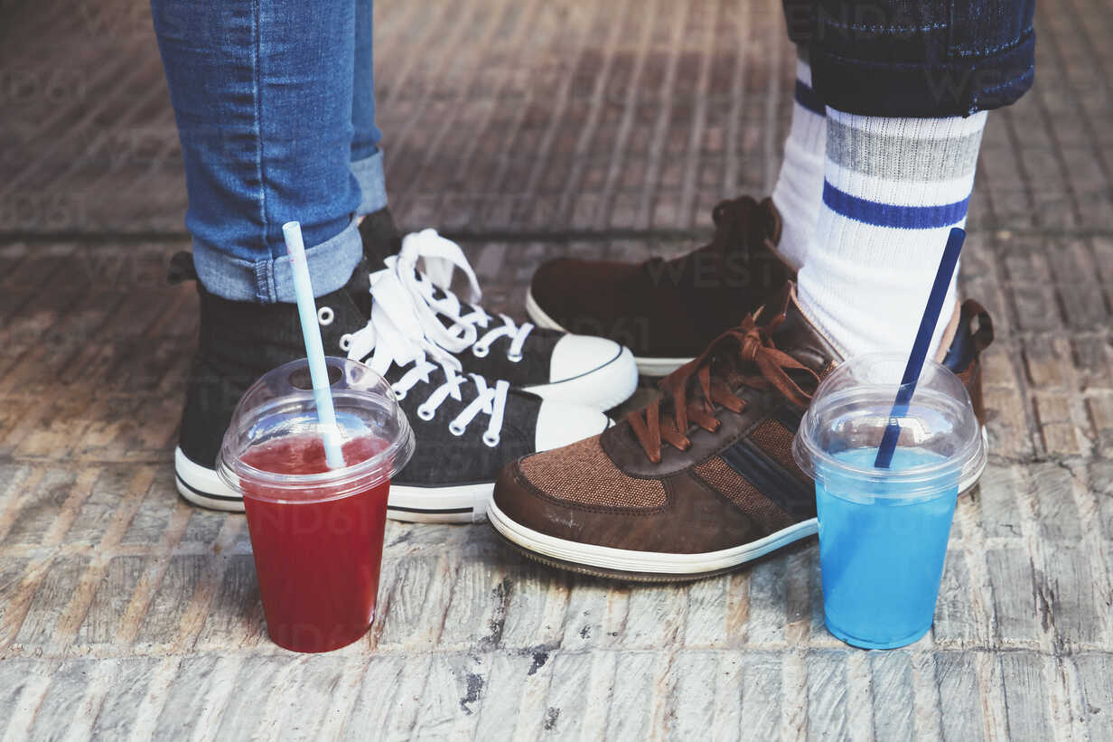 Plastic cups with soft drinks standing besides feet of young couple - RTBF000113 - Retales Botijero/Westend61