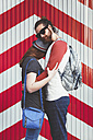 Young couple wearing sunglasses embracing on the street - RTBF000116