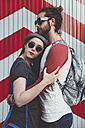 Young couple wearing sunglasses embracing on the street - RTBF000119