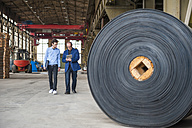 Two men walking in factory hall with rolls of rubber - DIGF000286