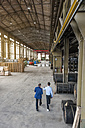 Two men walking through factory hall - DIGF000292