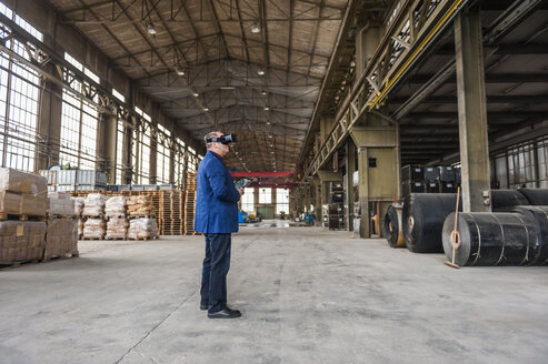 Manager standing in factory hall looking through VR glasses - DIGF000304