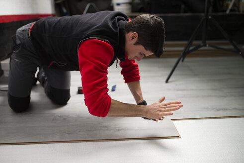 Young man placing a laminate floor - RAEF001052