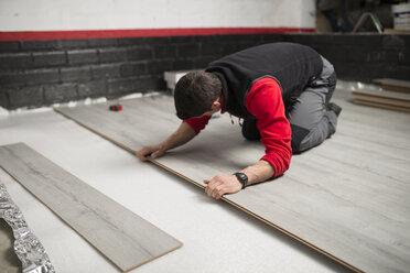 Young man placing a laminate floor - RAEF001055