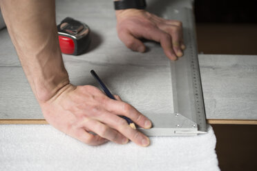 Man measuring with a angle measure, laminate floor - RAEF001061