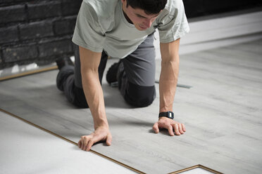 Young man placing a laminate floor - RAEF001067