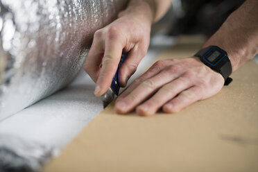 Young man cutting a insulating material for a laminate-flooring - RAEF001073