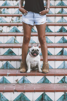 Dog standing between legs of owner on stairs - RTBF000130