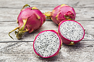 Sliced and whole dragon fruits on wood - LVF004753