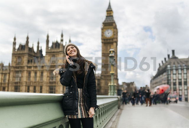 UK, London, happy young woman telephoning with smartphone in front of Palace of Westminster - MGOF001728 - Marco Govel/Westend61