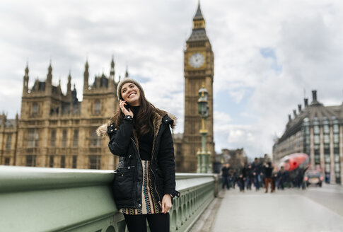 UK, London, happy young woman telephoning with smartphone in front of Palace of Westminster - MGOF001728