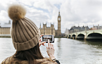 UK, London, back view of young woman taking picture of Westminster Parliament - MGOF001731