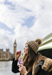 UK, London, young woman blowing soap bubbles - MGOF001734