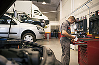 Mechanic repairs and examines the car engine - JASF000656