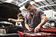 Men repairing engine car in workshop - JASF000671