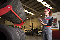 Woman takes stock of tires with digital tablet - JASF000680