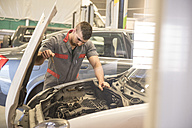 Mechanic repairs and examines the car engine - JASF000683
