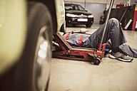 Car mechanic on creeper dolly at work in repair garage - JASF000695