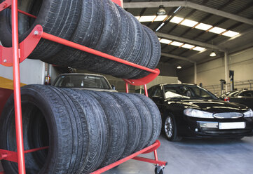 Tires in workshop and mechanic driving car - JASF000698