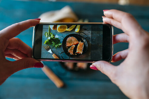 Closeup of hands taking a picture of salmon fillets with parsley and lemon - KIJF000325