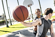 Two young men playing basketball on an outdoor court - LEF000105