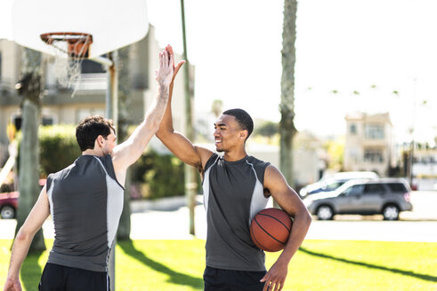Two young men high-fiving on outdoor basketball court - LEF000113