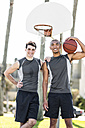 Portrait of two smiling young men on outdoor basketball court - LEF000116