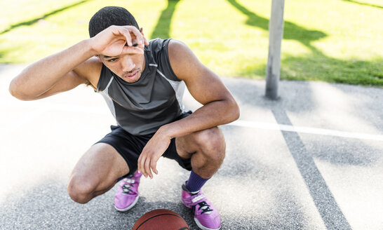 Basketball player crouching on outdoor court - LEF000119