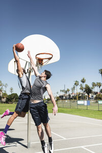 Two young men playing basketball on an outdoor court - LEF000122
