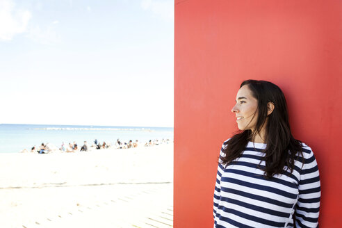 Spain, Barcelona, woman wearing striped sweater leaning against red wall looking to the beach - VABF000449