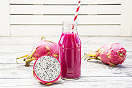 Glass bottle of dragon fruit smoothie and half of dragon fruit - LVF004765