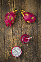 Glass bottle of dragon fruit smoothie and dragon fruits on wood - LVF004768