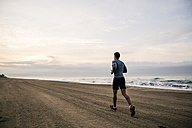 Young man running on the beach - EBSF001296