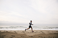 Young man running on the beach - EBSF001299