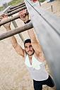 Young man exercising on monkey bars - EBSF001326