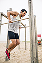 Young man exercising on bars on the beach - EBSF001329