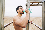 Athlete drinking water from bottle on the beach - EBSF001332