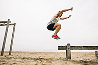 Young man jumping on the beach - EBSF001341