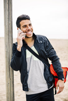 Smiling young man on cell phone on the beach - EBSF001359