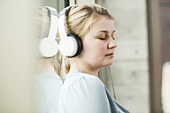 Relaxed young woman listening to music - UUF006997