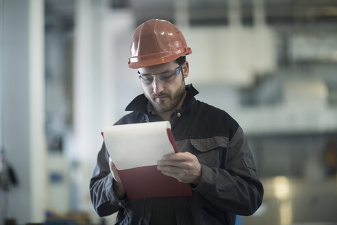 Young technician, working, clipboard - SGF002032