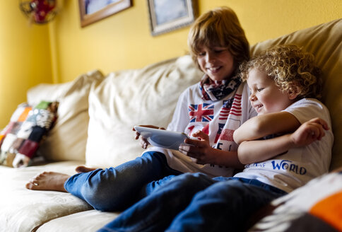 Two boys sitting on couch using digital tablet - MGOF001739
