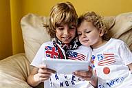 Portrait of two boys sitting on couch using digital tablet - MGOF001742