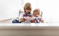 Two boys playing with digital tablet at home - MGOF001757